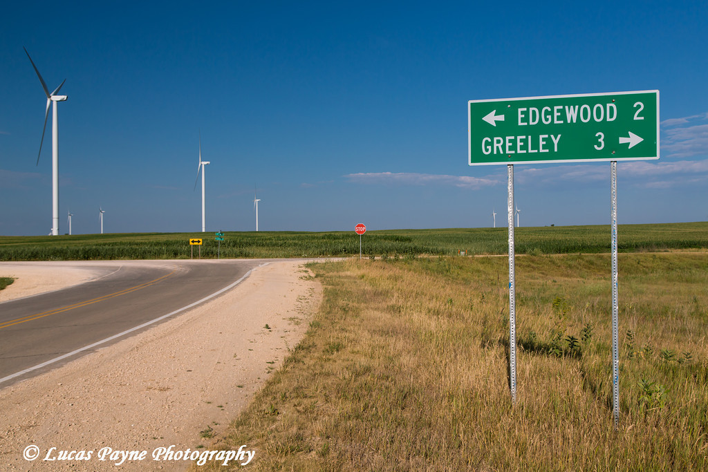 Road sign indicating miles to Edgewood and Greeley Iowa with Wind turbines from the Elk Wind Energy Farm in background<br /> <br /> July 08, 2012