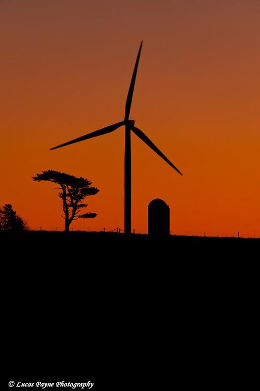 Elk Wind Energy Farm wind turbine and silo at sunrise near Edgewood in Eastern Iowa<br /> December 25, 2011