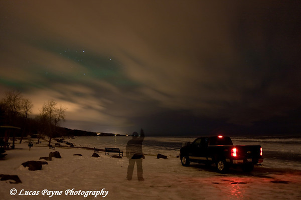 The Aurora Borealis (through the clouds) over Lake Superior, photographed at Kitchi Gammi Park just outside Duluth, MN.  For this image I tripped the shutter and during the exposure, ran to my truck and tapped the brake, then ran to the spot where you can see me standing and stood still for about 40 seconds, and back to the camera to close the shutter.