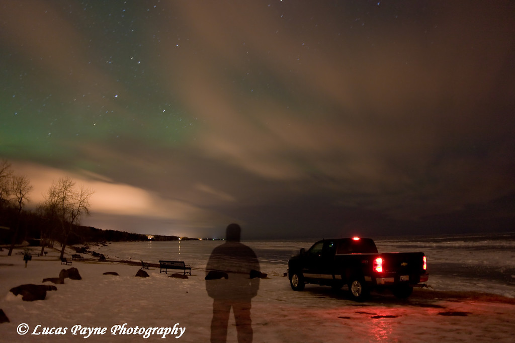 The Aurora Borealis over Lake Superior (through the clouds), photographed at Kitchi Gammi Park just outside Duluth, MN.  For this image I tripped the shutter and during the exposure, ran to my truck and tapped the brake, then ran to the spot where you can see me standing and stood still for about 40 seconds, and back to the camera to close the shutter.