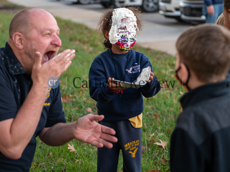 """Father Jeffery Dauses laughs at Avia Love, a kindergartner at Immaculate Heart of Mary School in Baynesville, after she pies herself in the face instead him during the """"Fool on the School"""" fundraiser. (Kevin J. Parks/CR Staff)"""