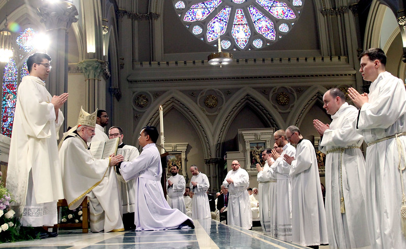 Cardinal Sean O'Malley conducts the Rite of Ordination as the other Deacon Candidates stand by. SUN/ David H. Brow