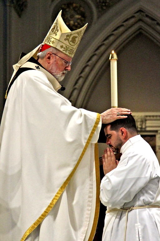 . Cardinal Sean O\'Malley places his hand on candidate Mr. Marcos Enrique during the Rite of Ordination. SUN/ David H. Brow