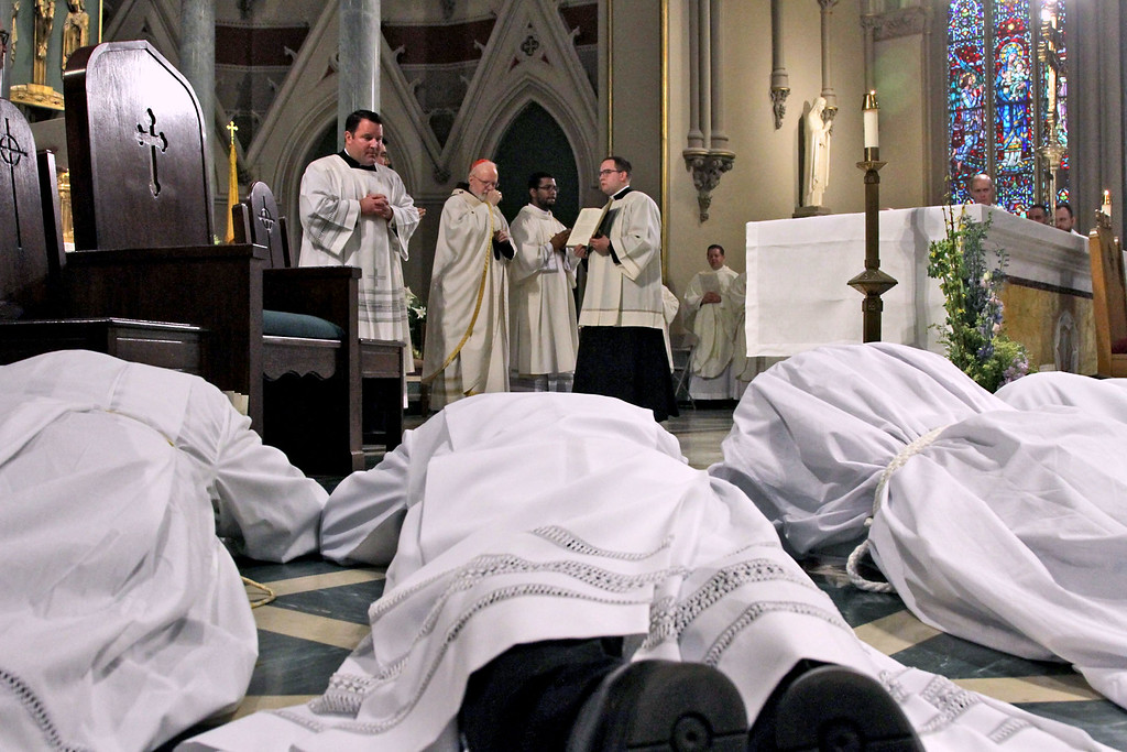 . Deacon candidates lie prostrate before the alter as a sign of their humble submission to God\'s will, during the Rite of Ordination. SUN/ David H. Brow