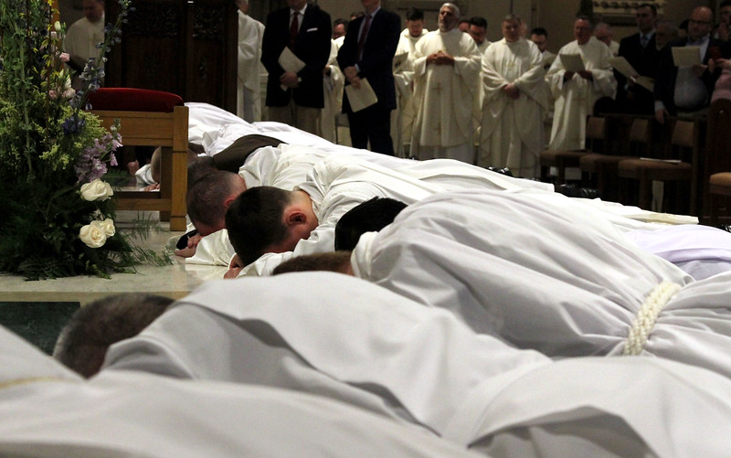 Deacon candidates lie prostrate before the alter as a sign of their humble submission to God's will, during the Rite of Ordination. SUN/ David H. Brow