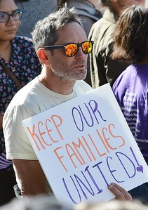 "Man holding sign ""Keep Oou Families Together"" at immigrant rights rally."