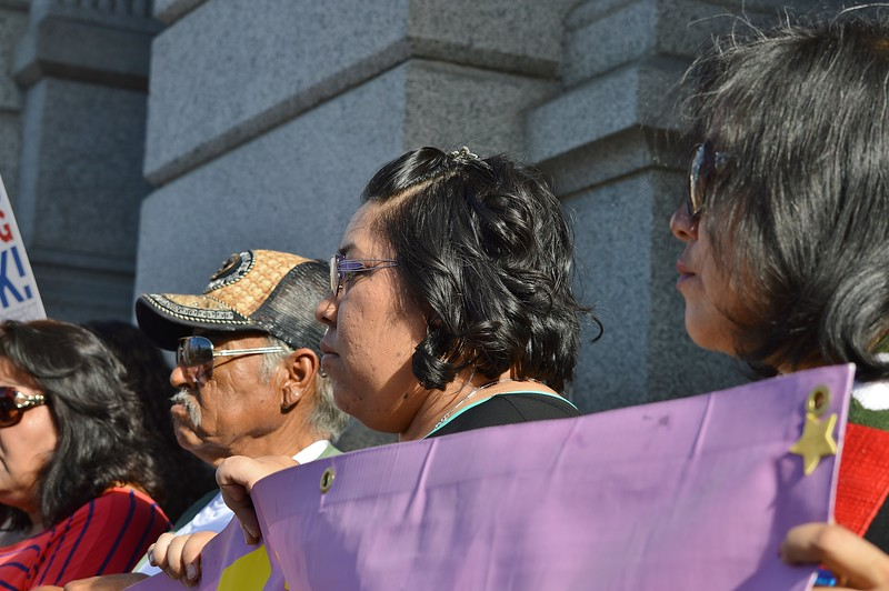 Three demonstrators listening to speaker at rally for immigrant rights.