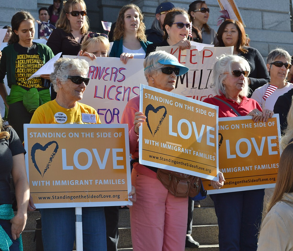 """Three women at immigrant rights rally hold signs that read """"Standing On the Side of Love""""."""