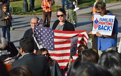 Woman holding large American flag listens to speaker at immigrant rights rally.