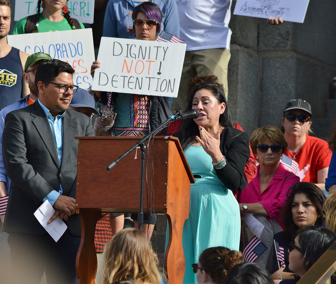 Hispanic woman gestures while speaking at rally for immigrant rights.