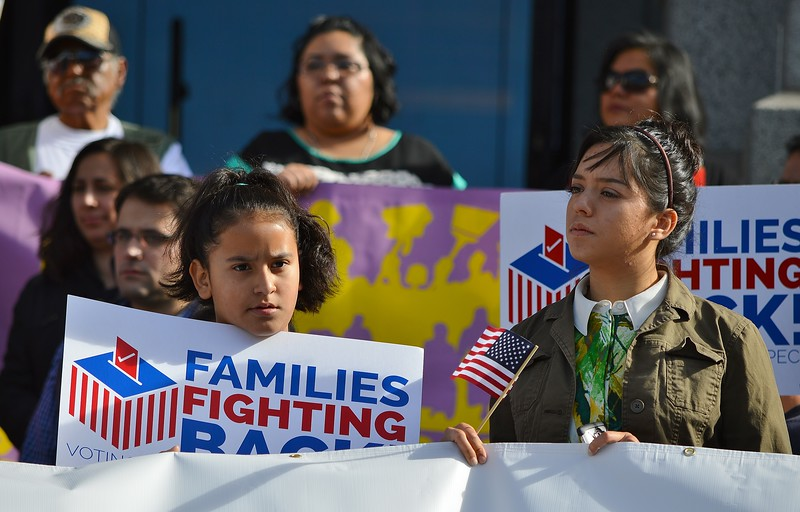 Two young girls listening to speaker at rally for immigrant rights.
