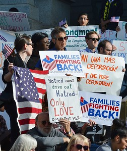 Group of people at immigration reform rally holding signs and American flags.