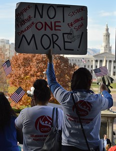 Woman holding American flag raises sign opposing deportations at immigrant rights rally, in background is Denver City/County Building.