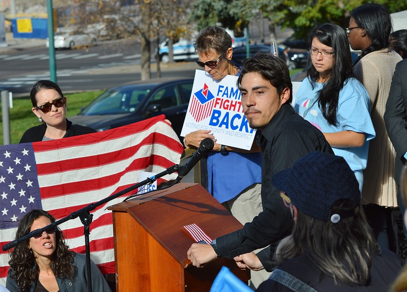 Young hispanic man speaking at a rally for immigrant rights in Denver.