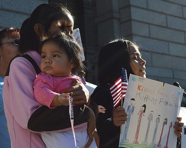 Young girl holding small child with American flag at immigrant rights rally.