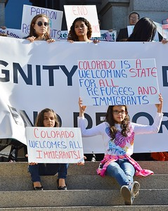 Two young girls sitting on steps with signs about immigrants and refugees, at immigrant rights rally.