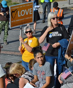 Demonstrators hold up signs at immigrant rights rally.