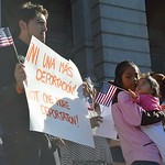 Young man holds American flag and sign against deportation at rally for immigrant rights.