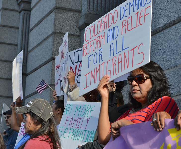 Woman hold sign for immigration law reform above her head at rally.
