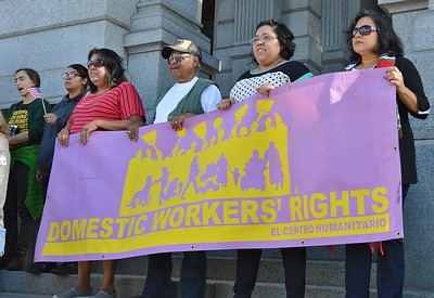 Group of domestic workers hold banner at rally for immigrant rights.