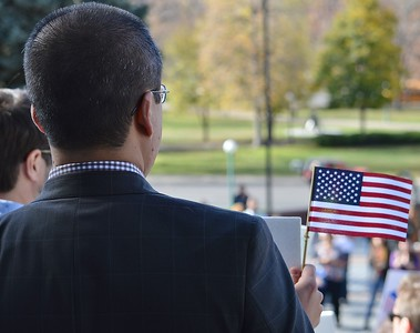 Man in suit holding small American flag at immigrant rights rally.