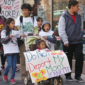 Hispanic mother with young children, one in stroller carrying sign, march in protest against deportations.