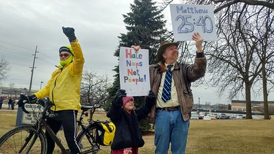 """Robert Osterman (right), 42 and a high school teacher from Clarkston stands with his daughter Kaylee protesting House Resolution-565, or the """"Save Christians from Genocide Act"""", co-sponsored by Rep. Mike Bishop while asking for Bishop to hold a town hall with his constituents, outside of Rochester High School in Rochester Hills on Tuesday, Feb. 21, 2017."""