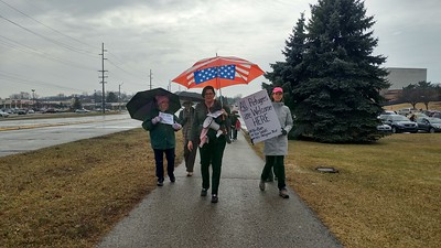 """Event organizer Heather Cogswell (center) walks with demonstrators protesting House Resolution-565, or the """"Save Christians from Genocide Act"""", co-sponsored by Rep. Mike Bishop while asking for Bishop to hold a town hall with his constituents, outside of Rochester High School in Rochester Hills on Tuesday, Feb. 21, 2017."""