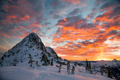 The sun rises, illuminating the sky behind a snow covered mountain.