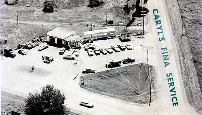 "Fina gas station and possibly car sales. This card does not have a caption but a handwritten note on the reverse says ""Caryl Baker, from Mille Roche, corner of power dam and Hwy 2  intersection."" —Clive Marin Collection"