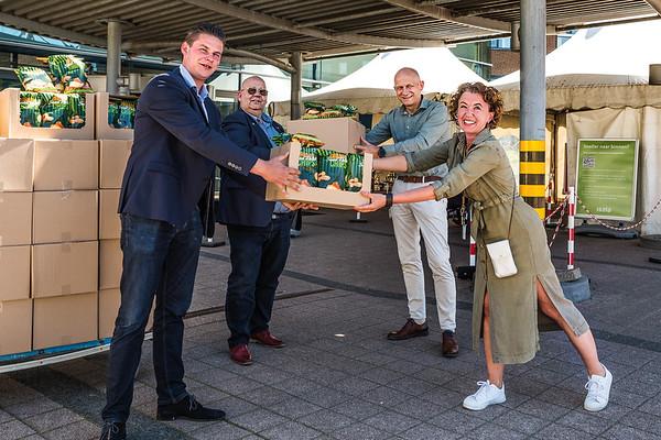 Guus van der Wende (l) en André Schaap van Farmforte overhandeigen 2000 zakken zoete aardappelchips aan het personeel van Isala Meppel.