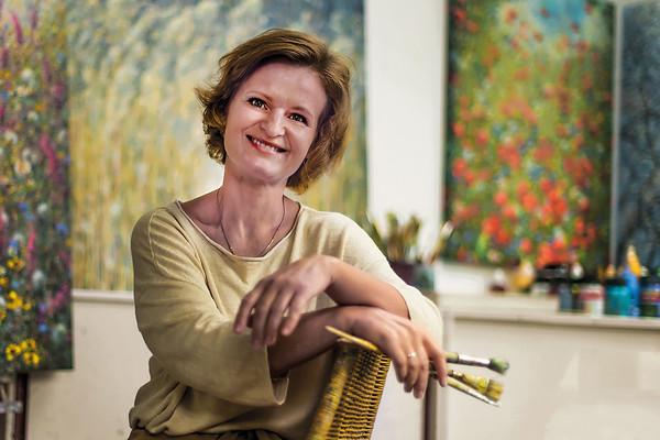 """Ala Khonikava, kunstenares, Meppel  Elk sprietje is de moeite waard  Ala Khonikava woont al jaren in Meppel en staat vooral positief in het leven. Dat uit zich onder andere in haar impressionistische en romantische schilderstukken die gewaardeerd worden in binnen- en buitenland. Het landschap speelt een hoofdrol in haar werk. Vormen, lijnen en contrasten van rietland, boomtakken of een veld met bloemen in het volle licht van de dag geven haar veel inspiratie. """"Elk sprietje is de moeite waard"""" zoals zij zelf zegt. De professionele kunstenares uit Wit-Rusland wil met haar werk een natuurlijk en persoonlijk accent aanbrengen in het kunstwerk voor de  particuliere of zakelijke opdrachtgever. Ze is uitgesproken belangstellend in zijn verhaal en beleving zodat ze daar iets van kan verbeelden in het schilderstuk. Zo zal het werk je ook persoonlijk 'raken' en je anders laten kijken naar de wereld om je heen. Ala vult aan: """"fijn als mijn werk een soort blikopener van emoties en herinneringen voor de kijkers kan zijn"""".   In het atelier van Ala aan de Nijeveenseweg bent u op afspraak van harte welkom. Kijk voor meer informatie eens op: www.alakhonikava.com"""