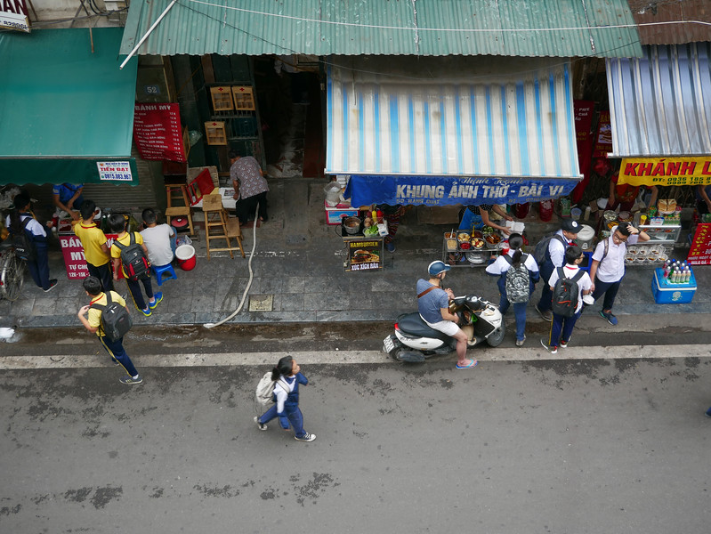 Schoolchildren buying breakfast before heading to their school, just in back of these shops