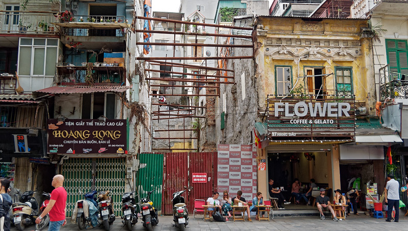 The partially-visible building with the Hoang Long sign in front is of a type commonly seen. Because buildings are taxed based on their width, many houses are extremely narrow but built to be three or four stories high.