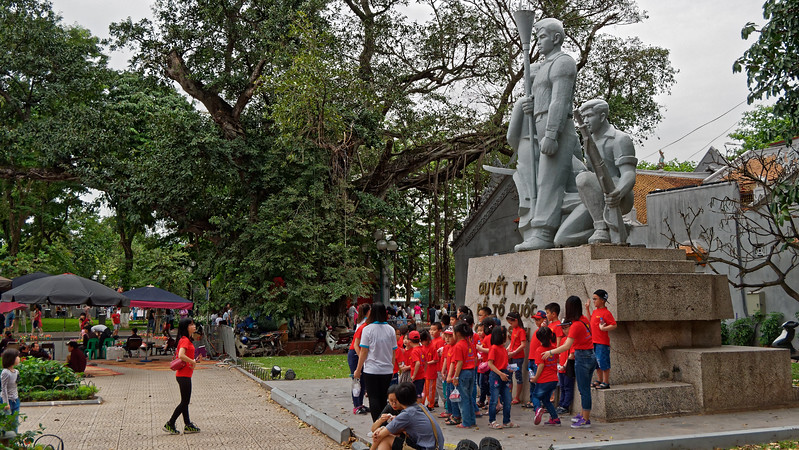 Schoolchildren gather for a group photo at the Martyrs' Monument, dedicated to the men and women who fought for the independence of Vietnam, near Hoan Kiem Lake