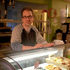 Richard Balogh, owner of Il Caffe Rifugio, standing behind a case of pastries that he makes right here.