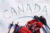 The word Canada written in snow with ski poles, goggles and hats (picture taken in fresh snow with directional winter sun).