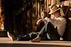 man hat sitting bare feet