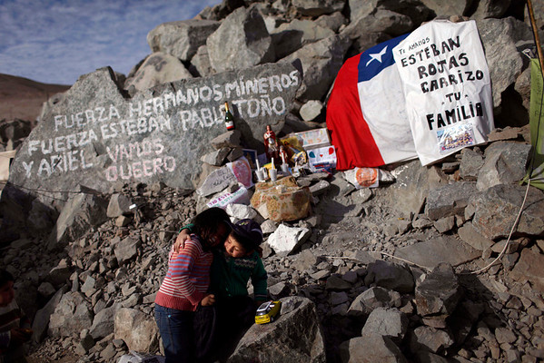 """Elias Sepulveda, right, embraces her cousine Katherine next to a tribute and support site with candles, flags and messages for their relatives Esteban and Pablo Rojas,  two of the 33 miners trapped at the collapsed mine San Jose in Copiapo, Chile, Monday, Aug. 23, 2010. The miners, who have been trapped since the shaft they were working in collapsed on Aug. 5, were confirmed to be alive Sunday when they were reached by rescue teams via a small hole through which they could pass messages and see the miners with a camera. The message at top left reads in Spanish """"Be strong brother miners, be strong Esteban, Pablo, Tono and Ariel. Let's go Queero"""" and at right """"We love you Esteban Rojas Carrizo, your family.""""  (AP Photo/Roberto Candia)"""