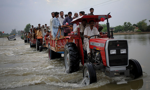 Tractor trolleys with families cross a flooded highway in Baseera, in central Pakistan, Tuesday, Aug. 24, 2010. Pakistan's medical system has been badly hit by weeks of flooding, with hundreds of health facilities damaged and tens of thousands of medical workers displaced, the prime minister said Tuesday as the country braced for the spread of disease. (AP Photo/Khalid Tanveer)