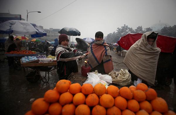 Afghan roadside fruit vendors wait for customers as it snows in Kabul, Afghanistan, Friday, Feb. 5, 2010 (AP Photo/Altaf Qadri)