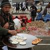 An Afghan street vendor man cooks cookies for sale in Kabul, Afghanistan, on Sunday, Feb. 21, 2010. (AP Photo/Musadeq Sadeq)
