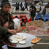 An Afghan street vendor man cooks cookies for sale in Kabul, Afghanistan, on Sunday, Feb. 21, 2010. (AP Photo/Musadeq Sadeq)