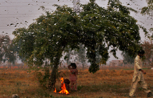 Pakistani girls sit around a fire to warm themselves during a rainy day on the outskirts of Islamabad, Pakistan, Friday, Feb. 5, 2010. (AP Photo/Muhammed Muheisen)