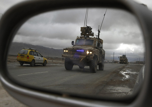 A convoy of foreign soldiers with the NATO-led International Security Assistance Force are reflected on a mirror of a vehicle in Kandahar, south of Kabul, Afghanistan, Monday, Feb. 8, 2010. (AP Photo/Allauddin Khan)