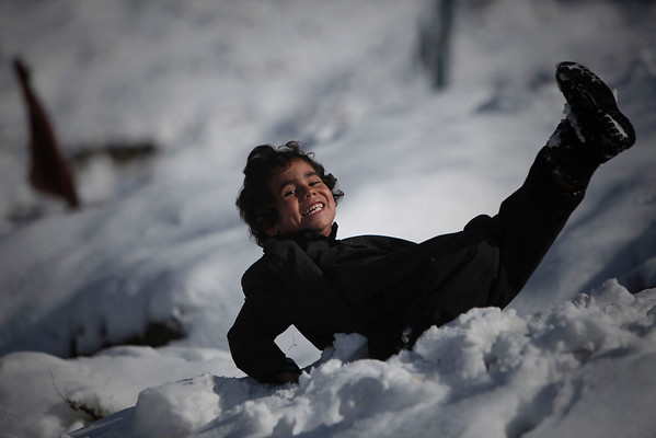 Sahil, an Afghan boy, laughs after he slipped on snow outside his house on a hilltop in Kabul, Afghanistan, Monday, Feb. 8, 2010. (AP Photo/Altaf Qadri)