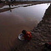 A young Pakistani girl, works to clean clothes using a small bowl in a ditch full of rain water, on the outskirts of Islamabad, Tuesday, Feb. 9, 2010. (AP Photo/Muhammed Muheisen)