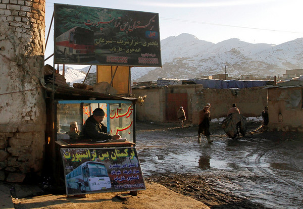 An Afghan man, who registers passengers' names, take notes at a bus travel agency called Turkistan Bus Transportation in Kabul, Afghanistan, on Tuesday, Feb. 9, 2010. (AP Photo/Musadeq Sadeq)