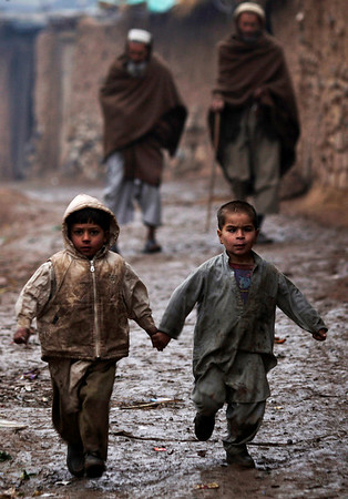 Two Afghan refugee boys run in an alley during a rainy day, in a poor neighborhood of Rawalpindi, Pakistan, Friday, Feb. 5, 2010. (AP Photo/Muhammed Muheisen)