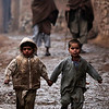 Two Afghan refugee boys run in an alley during a rainy day, in a poor neighborhood of Rawalpindi, Pakistan, Friday, Feb. 5, 2010. (AP Photo/Muhammed Muheisen)
